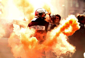 """A professional firefighter with the words """"Not happy"""" on his back waves a flare in front of a camera.."""