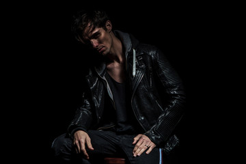 dramatic young man in leather jacket sitting and smiling