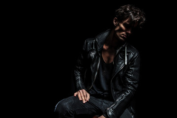 seated fashion model wearing leather jacket and looking away