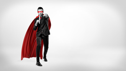 A businessman in a superhero red cape and a mask throwing punches in the air on white background in high contrast shot.