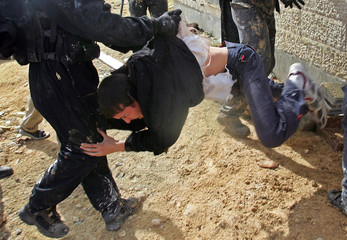 Israeli ultranationalist protester is lifted by Israeli police officer during clashes in Amona