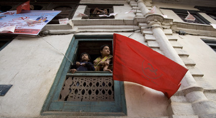 The Communist Party of Nepal (Maoist) flag waves from a balcony as residents watch a campaign rally in Kathmandu