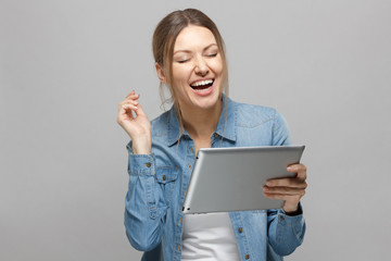 Portrait of attractive european female, holding tablet, laughing with opening mouth, while posing against grey background.