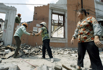 CHINESE WORKERS PASS BRICKS FROM DEMOLISHED HOUSES IN SHANGHAI.