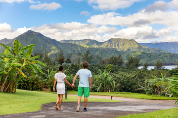Couple tourists walking on Hawaii vacation. Two young people relaxing in Hanalei Bay resort in Kauai, Hawaii travel beach destination with Kauai mountains in the background.