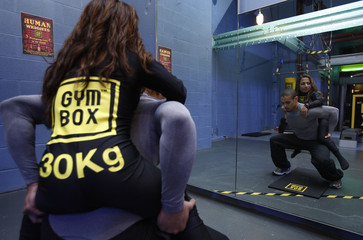 A fitness instructor does some squat exercises for photographers using a human weight at a Gymbox gym in London