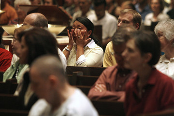 Molly Shelton wipes tears from her eyes as she prays for the victims involved in the I-35 bridge collapse at St. Olaf Catholic Church in Minneapolis