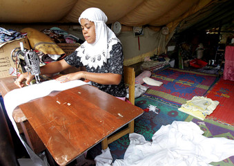 A woman sews inside tent for tsunami survivors near town of Lam No on west coast of Aceh province
