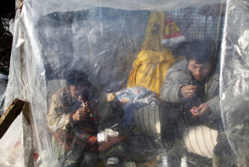 Chinese workers smoke inside a makeshift shelter as they camp outside the Chinese embassy in Bucharest