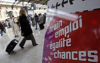 A commuter walks past a sign showing the way to the train for employment and equality of chances at the Marseille's railway station