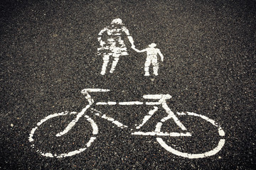 painted sign on asphalt, bicycle woman with child