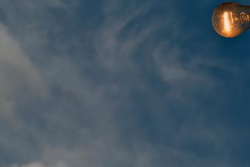 Enabled light bulb on blue sky background
