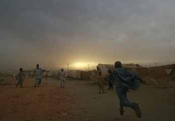 Internally displaced boys play in a dust storm at the UNHCR (United Nations High Commission for Refugees) Yar Hussain camp in Swabi district