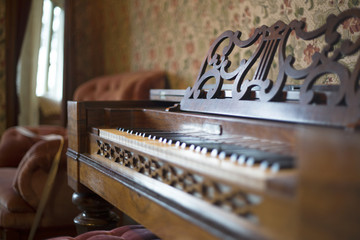 Close Up Selective Focus Organ/Piano, Shallow Field of Depth with Wallpaper in Background Rose Colored Chair (HDR Image)