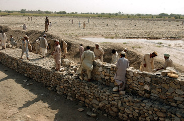 Afghan workers build stone wall for flood project funded by US in Nangarhar province east of Kabul