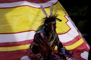 A native dancer is silhouetted against a colorful teepee during a ceremony in downtown Calgary, June..