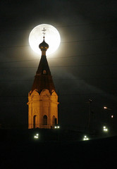 Paraskeva Pyatnitsa orthodox chapel, built in the 17th century, is seen with the full moon in the background at Karaulnaya Hill in the Siberian city of Krasnoyarsk