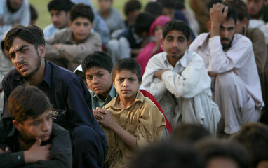 Internally displaced people, fleeing military operations in Buner, squat in a queue for tea at a UNHCR camp (United Nations High Commission for Refugees) in Takht Bai