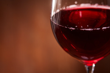 Elegant and fragile wineglass of tasty red wine against brown wooden background close-up.