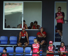 Canada players watch as they lose to England in their World Cup cricket match in Gros Islet