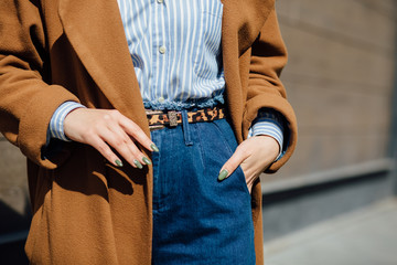 Closeup of hand of stylish woman in brown coat blue striped shirt, blue jeans with tiger pattern belt. Fashionable girl on the street. Female fashion Wall mural