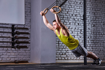 Young athlete man working out in gym pull ups with gymnastic rings against brick wall in the cross fit gym.