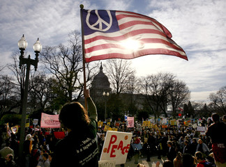 An anti-war demonstrator waves a US flag with a peace symbol on it in Washington