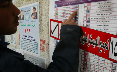 Man studies a poster promoting the forthcoming elections in Basra in southern Iraq.