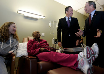 Woman and cancer patient talk with cyclist Armstrong and New York City Mayor Bloomberg in Austin