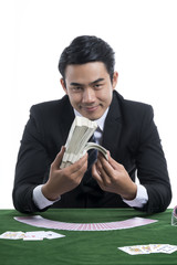 The handsome man in black suit holding piles of dollars in hands on casino desk