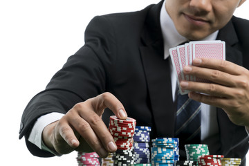 Close up at handsome man in black suit is putting piles of chips and holding poker card