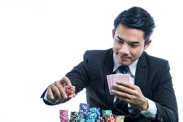 Portrait young man in black suit is putting stack of chips and holding poker card