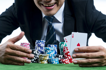 The poker gambler is showing a pair of aces and smiling hold bet a large stack with arms