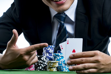 The poker gambler use finger pointing to a pair of aces and hold bets a large stack with arms