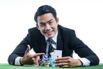 Portrait the poker gambler use finger pointing to a pair of aces and bets on green table