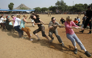 Tourists struggle as they take on Rajasthani men in a tug-of-war at the Pushkar fair, in India's desert state of Rajasthan