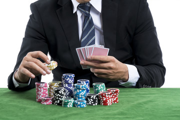 The man in black suit holding some chips for into the bets