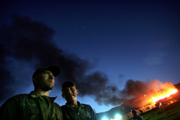 Iranian soldiers stand while narcotic drugs burn in Tehran.