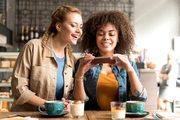 Smiling women watching at mobile