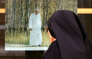 A nun walks past a poster depicting Pope John Paul II close to Saint Peter's Square at the Vatican.