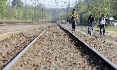 Children walk next to the railway track during a strike by railway workers in Isaszeg
