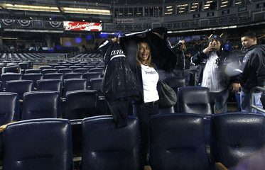 Fans stand in the seats at Yankee Stadium after rain forced the postponement of Game 6 of Major League Baseball's ALCS playoff series in New York