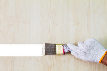 Man's hand wearing white glove holding old grunge paintbrush and painting on wooden wall