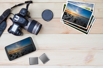 DSLR camera, smartphone, photos and memory card on wooden background