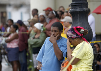 People wait outside as polices and rescue teams search for a person trapped in a building in front of Havana's Malecon