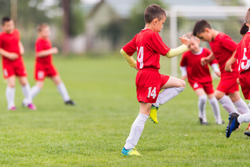 Kids soccer football - children players exercising before match on soccer field