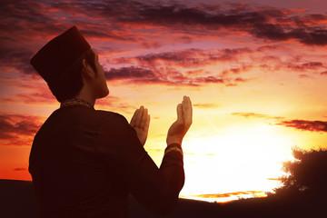 Back view of asian muslim man with black cap praying