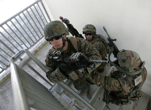 U.S. Marines equipped with Multiple Integrated Laser Engagement System (MILES) navigate the stairs of a building during a Force-on-Force military operation at the U.S. army's Rodriguez range in Pocheon
