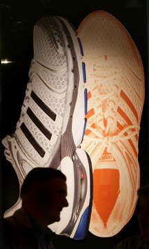A shareholder of Adidas Group is silhouetted in front of shoes before shareholder meeting in Fuerth