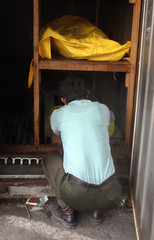 A victim of Saturday's bomb attacks is placed in a cooling container at the morgue at Sanglah Hospital in Denpasar